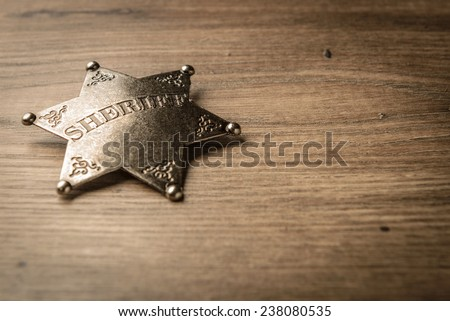 Vintage Wild West Sheriff badge on a rustic wood background. - stock photo
