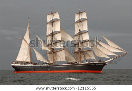 Vintage windjammer tall ship with full sails against a dark gray sky and sea - stock photo