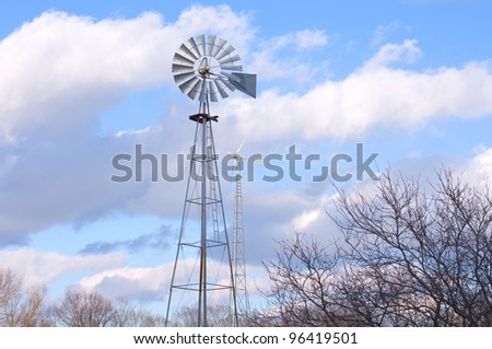 Vintage windmill and newly built wind turbine atop towers
