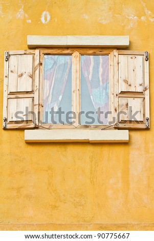 Vintage window on yellow cement wall can be used for background - stock photo