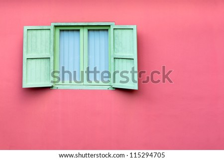 Vintage window with green retro wooden shutters on pink wall, Singapore - stock photo