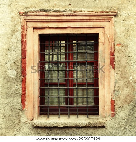 Vintage window with steel bars on old dirty damaged wall building. Square toned image, instagram effect - stock photo