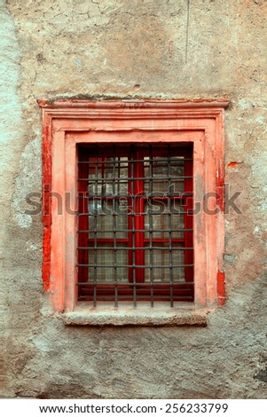 Vintage window with steel bars on old dirty damaged wall building, toned image - stock photo