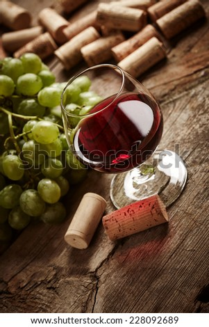 Vintage wine still life with corks and grape on wooden background - stock photo
