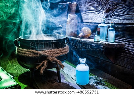 Vintage witcher cauldron with blue potions for Halloween