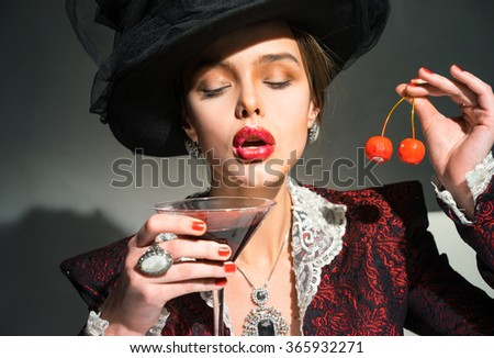 Vintage woman drinking a martini glass with cherry - stock photo