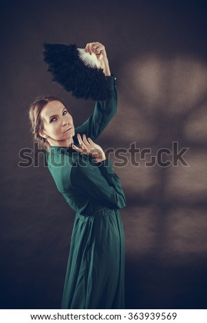 Vintage woman retro style dancing with black feather fan on dark - stock photo