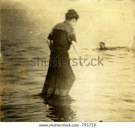 Vintage woman wading in towards submerged swimming man. Circa 1910. Photo very old with many scratches, fading, and solarizing qualities. - stock photo