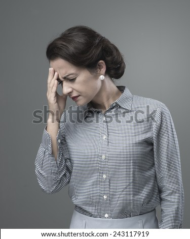 Vintage woman with headache touching her forehead - stock photo