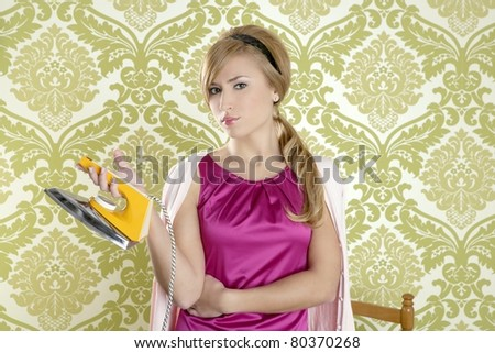 vintage woman with retro clothes iron like an humor housewife over  wallpaper - stock photo