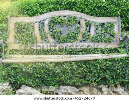 Vintage wood bench in garden. Vintage wooden bench in beautiful pattern put against in bush and green tree fence with grass covered background in green park - stock photo