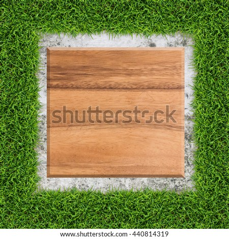 Vintage wood board in green grass frame with concrete texture background.