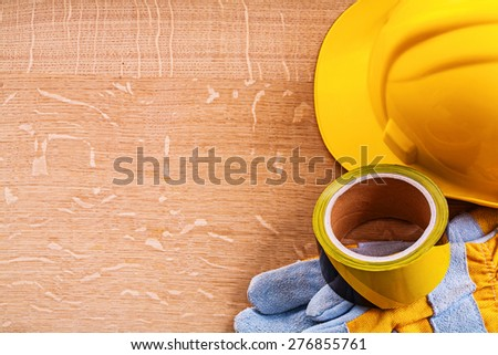 Vintage wood board with safety tape protective gloves and hard hat construction concept  - stock photo
