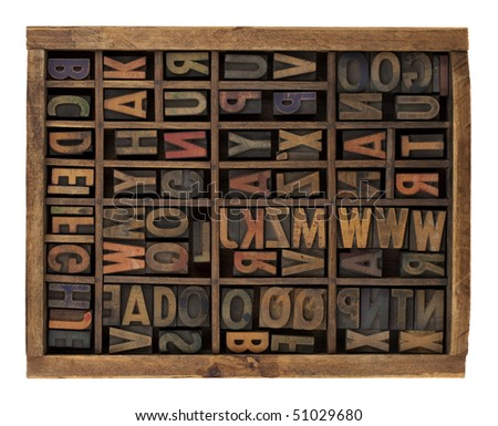 vintage wood letterpress types, stained by ink, placed randomly in typesetter drawer, isolated on white - stock photo
