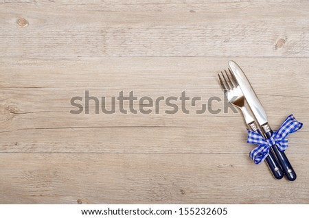 Vintage wood with knife and fork and blue checkered bow - stock photo
