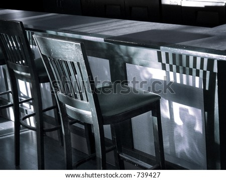 Vintage wooden bar stool casts shadow on bar in this blue-toned black & white shot.