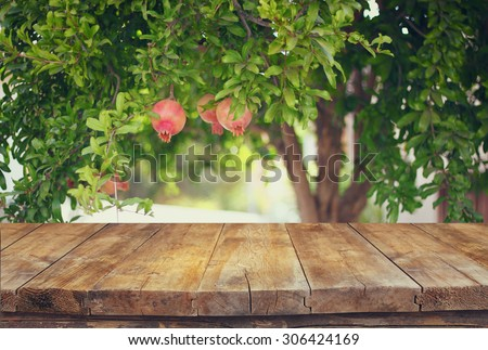vintage wooden board table in front of dreamy pomegranate tree landscape. retro filtered image - stock photo