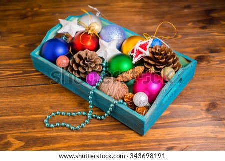 vintage wooden box with Christmas decoration, tinsel,  pinecones, stars and balls on wooden background, closeup  - stock photo