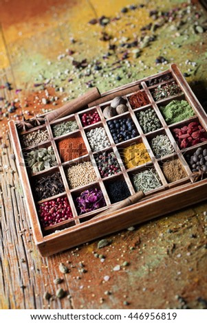 vintage wooden box, with many compartments, filled with spices, over old wooden table, sprinkled with spices, abstract compositions,
