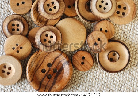 Vintage wooden buttons on handwoven cotton fabric.  Natural side lighting to emphasize textures. - stock photo