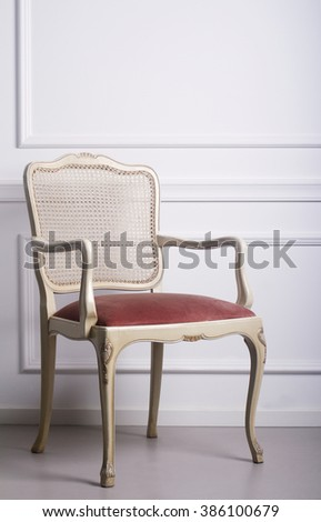 Vintage wooden chair against a white elegant interior wall