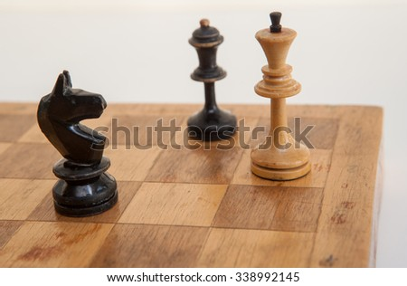 Vintage wooden chess on a wooden chess board. Mate for white king.