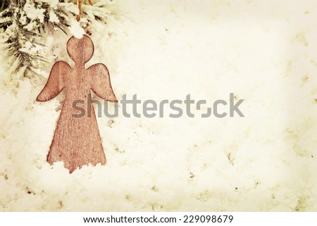 Vintage wooden Christmas angel decoration on snow background - stock photo