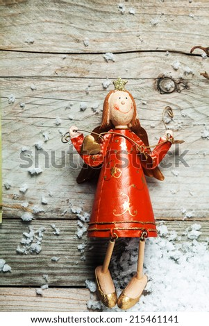 Vintage wooden Christmas angel in a colorful red dress in country crafts style on an old wooden background with copyspace - stock photo