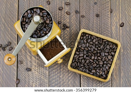 Vintage wooden coffee hand grinder with ground coffee inside next to a wooden box full of very dark roasted Robusta coffee beans - stock photo