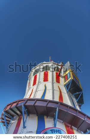 Vintage wooden fairground helter skelter against a clear blue sky and taken from a low angle - stock photo