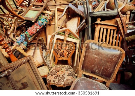 Vintage wooden furniture in trash warehouse of antique market. Retro background - stock photo