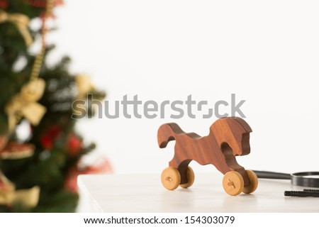 Vintage Wooden Horse on Santa's work table, Christmas Tree on background - stock photo