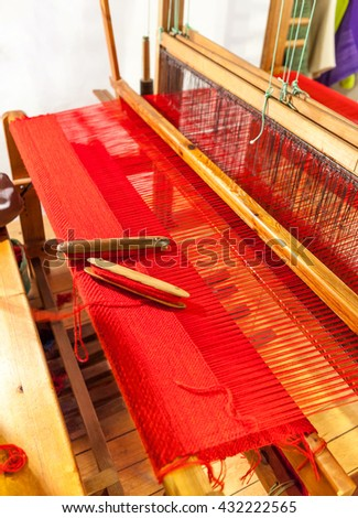 Vintage wooden loom weaving prepared for the red carpet. Wooden weaving shuttle on an old manual weaving machine - stock photo