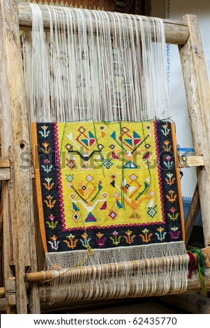 vintage wooden loom with half knit colored carpet on threads - stock photo