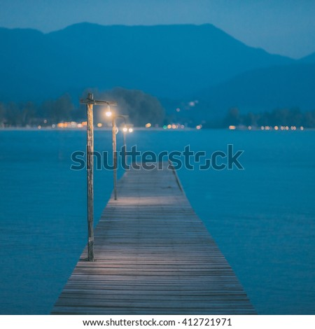 Vintage wooden pier at twilight with tropic island mountains covered in dusk mist fog across the bay. Classic photography landscape. Postcard travel inspiration. Vacation wallpaper. Vintage effect.