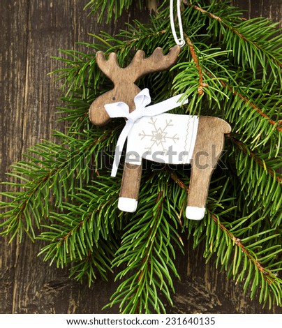 Vintage Wooden Reindeer Christmas Decoration and Green Fir Tree Branches - stock photo