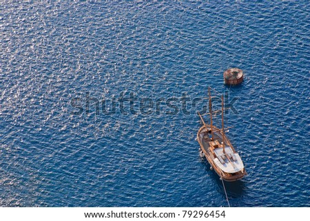 Vintage wooden sailing boat sailing towards the island of Santorini. Sea background. - stock photo