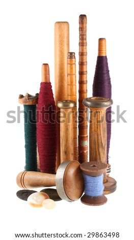Vintage wooden spools, vintage buttons, and sewing implements, isolated on white background