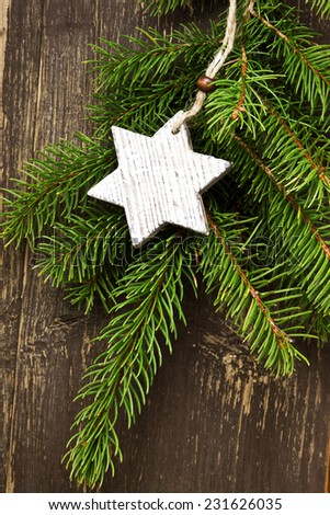 Vintage Wooden Star Christmas Decoration with Fir Tree Branches on Wooden Background - stock photo