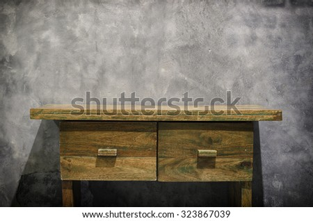 Vintage wooden table with gray wall.