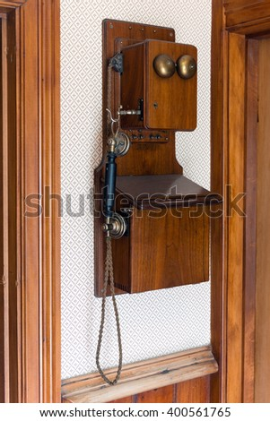 Vintage wooden telephone hung of a wall - stock photo