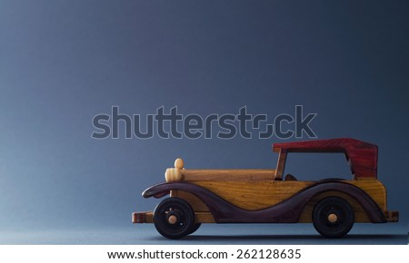 Vintage wooden toy car over dark blue background, image with negative space or copy space. - stock photo