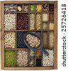 vintage, wooden typesetter case with variety of beans, lentils, peas, grains and seeds with a scoop of pinto - stock photo