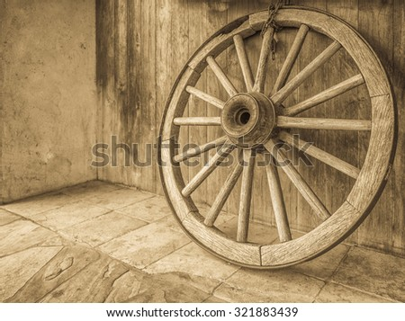 Vintage wooden wagon wheel with spokes, axle, and an iron rim,  in tones of black, white, and gray/grey. - stock photo