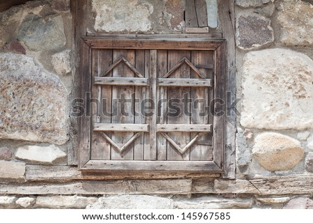 Vintage wooden window on old stone wall - stock photo