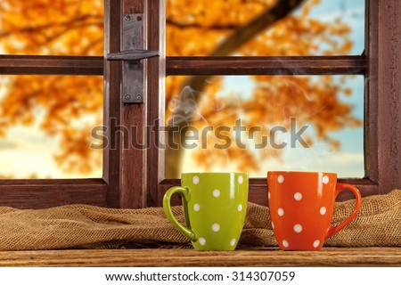 Vintage wooden window overlook autumn trees, shot from cottage interior with cups of tea - stock photo