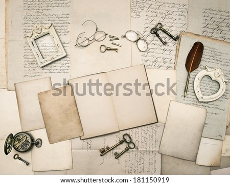 vintage writing accessories, glasses, keys, open book, old papers, letters and photo frames. documents and manuscripts - stock photo