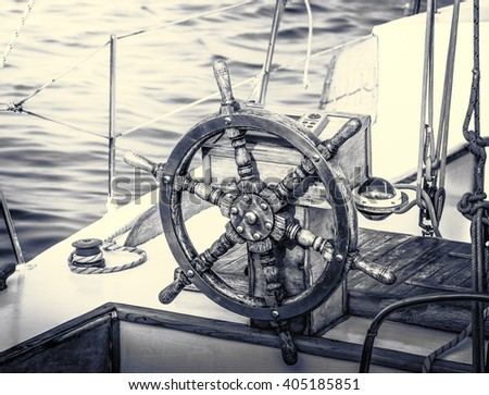 Vintage yacht in retro style. Steering wheel on the old sailboat. Sea voyage of the sailing vessel. Travel at sail boat with a wooden helm in front. Ship wheel on the old yacht. - stock photo