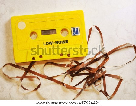 Vintage yellow musicassette with damaged tape. Selective focus. - stock photo