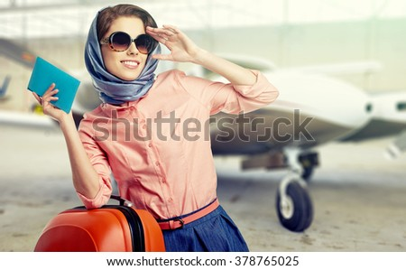 Vintage young female passenger at the airport (shallow DOF; color toned image) - stock photo
